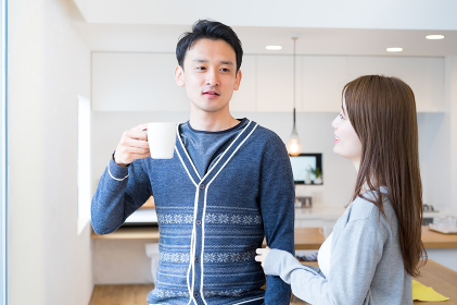 朝のコーヒーを飲みながら会話する幸せなカップル