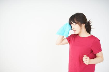 スポーツ中に汗を拭く若い女性