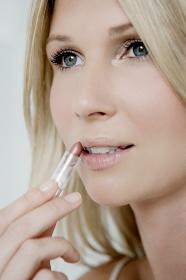Woman putting on lipstick.