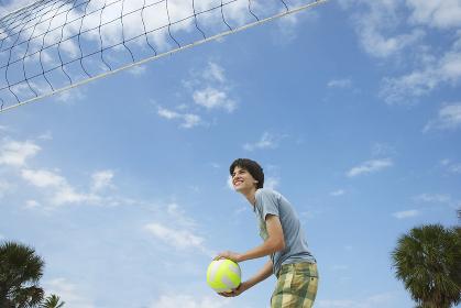Teenage Boy Playing Beach Volleyball