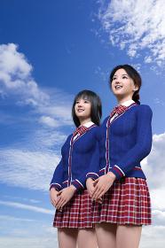 二人の女子高生が笑顔で明るい将来を見据えて雲が浮かぶ青い空を見つめている