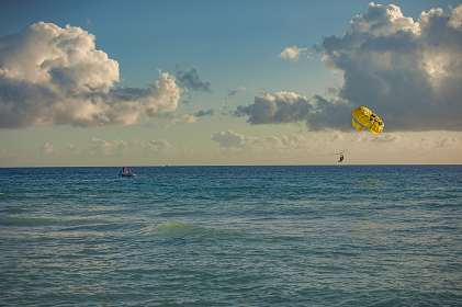 Paraglider in the sea at sunset