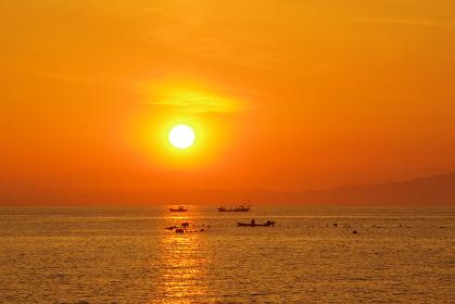 朝日の光の中、漁をする風景