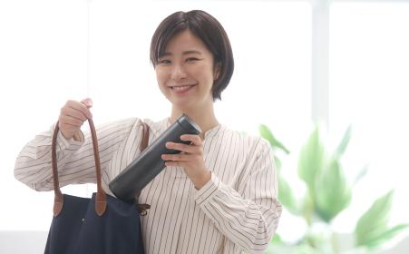 鞄から水筒を取り出す女性