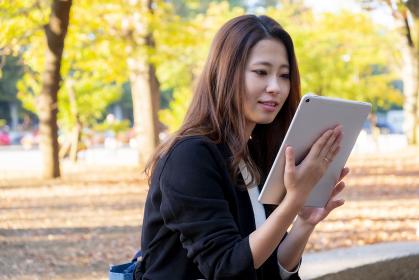 【東京都】屋外でタブレットを操作する女性【2020年 紅葉】