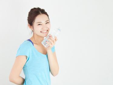 スポーツで水分補給をするアジア人女性