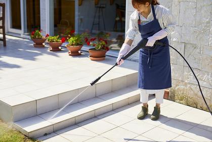 高圧洗浄機で掃除をする日本人女性