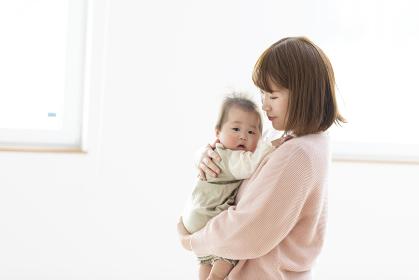 明るい部屋の中で赤ちゃんを抱っこするお母さん
