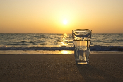 夕暮れの海と水が入ったグラス