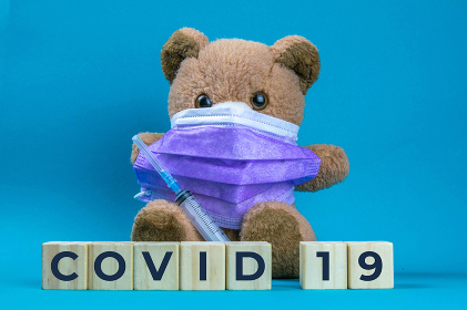 Covid 19. Coronavirus. Big teddy bear are sitting in blue medical masks on a blue background, concept of protection from respiratory disease, virus, and individual respiratory protection