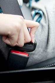 シートベルトを装着する女性の手元