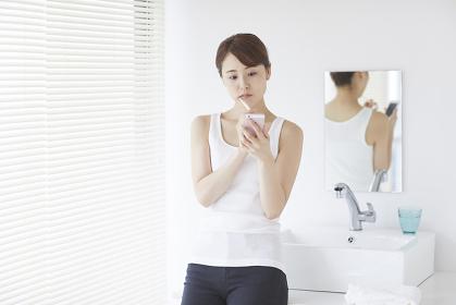 歯を磨きながらスマートフォンを見る日本人女性