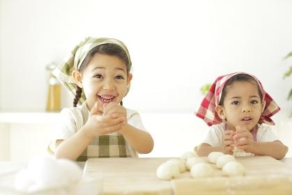 ピザ生地を丸める小さな女の子たち
