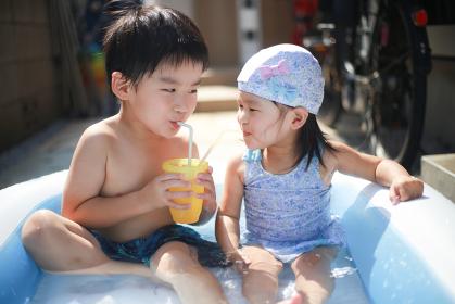 ビニールプールで仲良く飲み物を飲む子供たち