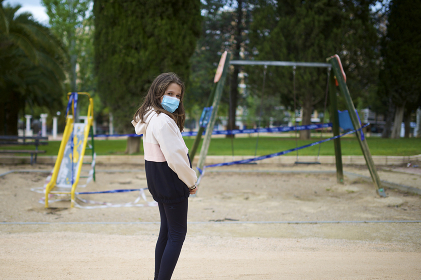 Little girl with surgical mask in a public park.
