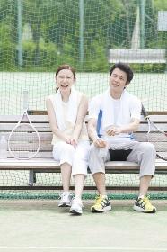 テニスコートのベンチで談笑する男女