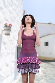 ピンクのタンクトップにピンクの花柄のフリルスカートを着用したウェーブのある黒髪ボブヘアの女の子が白い建物が並ぶ場所で両手の人差し指を上に向けて上を見上げているポーズ