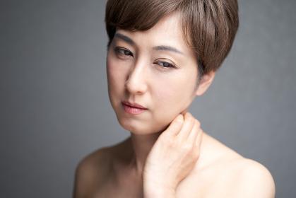 首筋に痛みを感じる中年の日本人女性