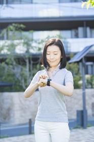 屋外でスマートウォッチを操作する中年女性