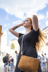 Ginger woman in dress putting tidy her hair in sunny day with blue sky