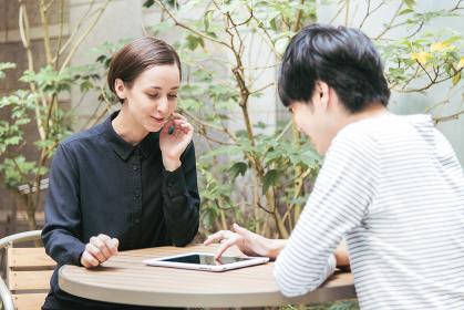 屋外のテラスでタブレットPCを使う外国人の男女(国際化イメージ)