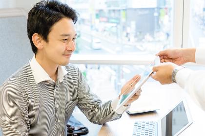飲食店でタブレット端末のメニューを見るビジネスマン