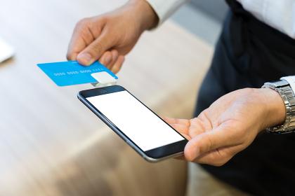 スマートフォンでクレジットカードの決済する店員(キャッシュレス・手元)