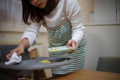 子供の食べこぼしを片付ける母親