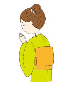 手を合わせ祈る着物姿の女性