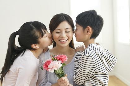 花束を持つお母さんにキスをする子どもたち