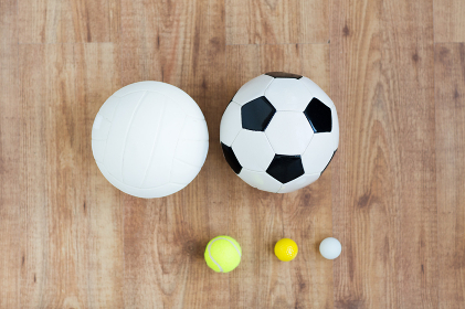 close up of different sports balls set on wood