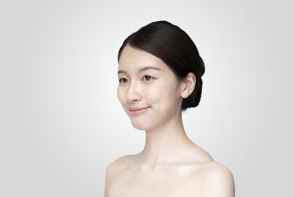 リラックスした表情で白い背景の前に立つ若い女性