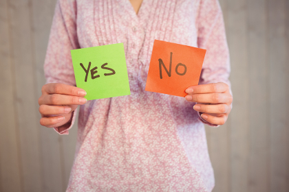 Woman holding yes and no cards