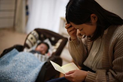 貯金通帳を見て悩む母親