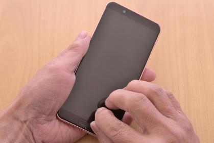 スマートフォンを操作するシニアの手