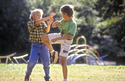 Parkszene, 2 Jungen im Alter von 8-10 Jahren kaempfen miteinander im Spiel