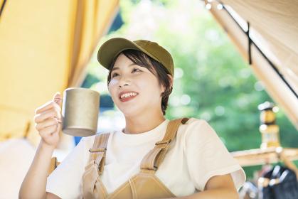 ソロキャンプイメージ・お酒を飲む若い女性