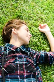 芝生に寝転がる女性(リラックスイメージ)