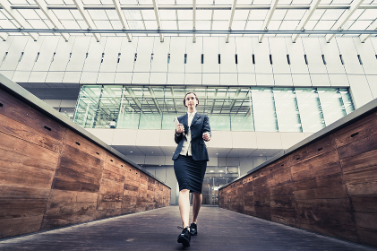 タブレットPCを手に歩く女性(ビジネスイメージ)