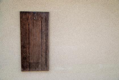 白い壁に吊り下げた古びた木の板