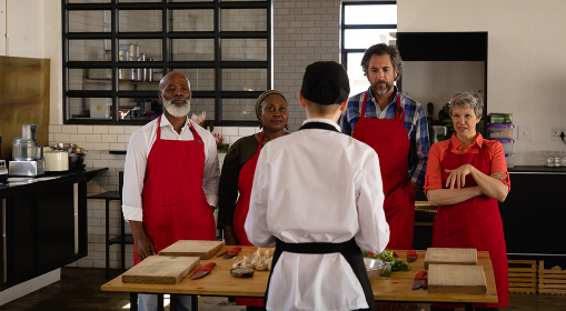Front view of a multi-ethnic group of Senior adults at a cookery class, the diverse adult students listening to instructions from a Caucasian female chef wearing chefs whites and a black hat and apron, standing around a wooden table of ingredients wearing red aprons