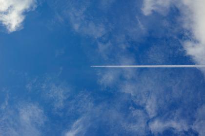 真っ直ぐな飛行機雲と白い雲のある秋の青空