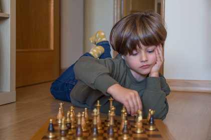 5 Year Old Boy Playing Chess. The Game Of Concentration And Strategy.