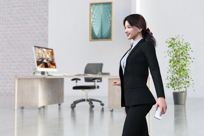 絵画と観葉植物があるおしゃれなオフィスを黒いスーツ姿の女性社員がクライアントとの電話を終え歩く
