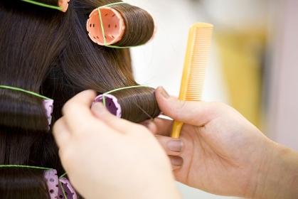 女性の髪にパーマをかける美容師の手元