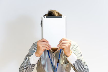 タブレットPCで顔を隠す男性(コンセプト画像)