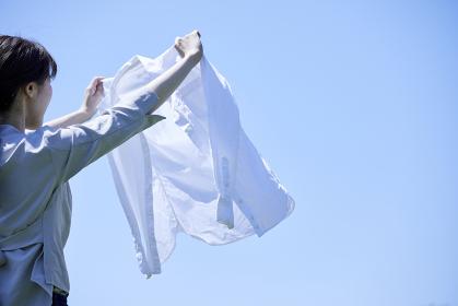 白いシャツを洗濯する若い女性