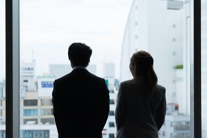 窓際に立つ2人(ビジネスイメージ・眺める・男性・女性)