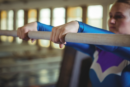 Female gymnast practicing gymnastics on the horizontal bar in the gymnasium