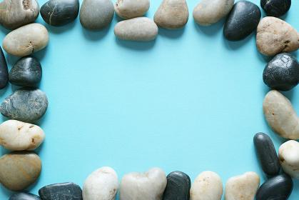 青い紙の背景に置いた複数の小石のフレーム。平置きの俯瞰撮影。